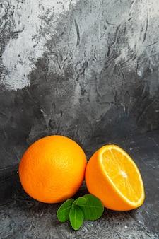 Vue verticale d'oranges entières et coupées en deux sur fond gris