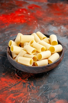 Vue verticale des pâtes non cuites à l'intérieur du pot sur fond noir