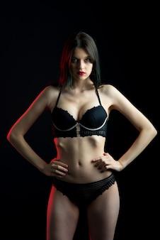 Vue verticale photo belle dame timide en culotte de soutien-gorge boudoir bikini en dentelle. espace noir tendre maigre mince isolé.