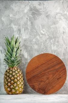 Vue verticale d'une planche à découper entière d'ananas doré frais debout sur une surface en marbre