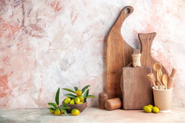 Vue verticale de planches à découper brunes en bois de différentes tailles et formes debout sur des kumquats muraux dans de petits pots sur un mur coloré