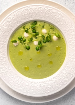 Vue verticale de la purée de soupe maison de pois verts, lait de coco avec mini fromage mozzarella en blanc