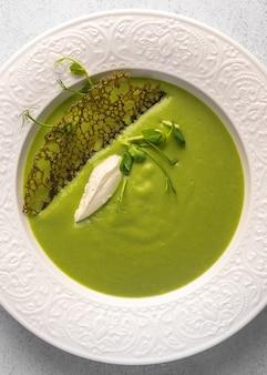 Vue verticale de la purée de soupe maison de pois verts et lait de coco avec tuil et quenelle au fromage