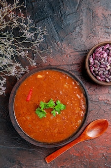 Vue verticale de la soupe aux tomates classique dans un bol brun haricots et cuillère sur des images de table de couleurs mélangées