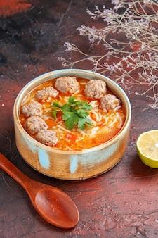 Vue verticale de la soupe de boulettes de viande avec des nouilles dans un bol marron cuillère au citron sur fond sombre
