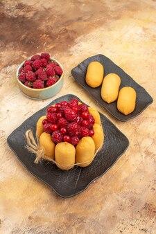 Vue verticale de la table avec un gâteau cadeau et des fruits pour les invités sur une table de couleurs mixtes