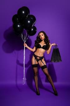 Vue verticale de la taille du corps sur toute la longueur de belle jolie dame aux cheveux ondulés mince tenant en main l'achat de nouveaux vêtements posant isolé sur fond de couleur lilas violet violet vif brillant