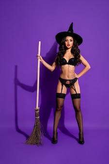Vue verticale de la taille du corps sur toute la longueur d'elle elle belle jolie fille aux cheveux ondulés magnifique avec balai magique automne octobre isolé sur fond de couleur lilas violet violet vif brillant