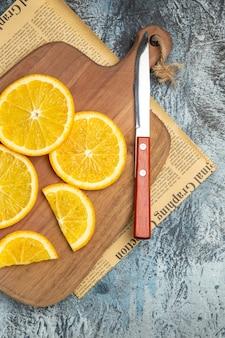 Vue verticale de tranches de citron frais avec couteau sur planche à découper en bois sur papier journal sur fond gris