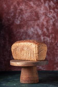 Vue verticale de tranches de pain noir sur une planche à découper sur fond dégradé de couleurs mélangées avec espace libre