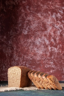 Vue verticale de tranches de pain noir sur une serviette de couleur nude sur fond de couleur marron