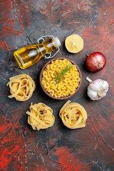 Vue verticale de trois pâtes spaggeties et papillons non cuits dans un bol brun et oignon vert citron ail bouteille d'huile sur fond de couleur mixte