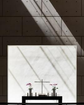 Vue verticale des vases et une croix sur une table dans une pièce avec mur en béton