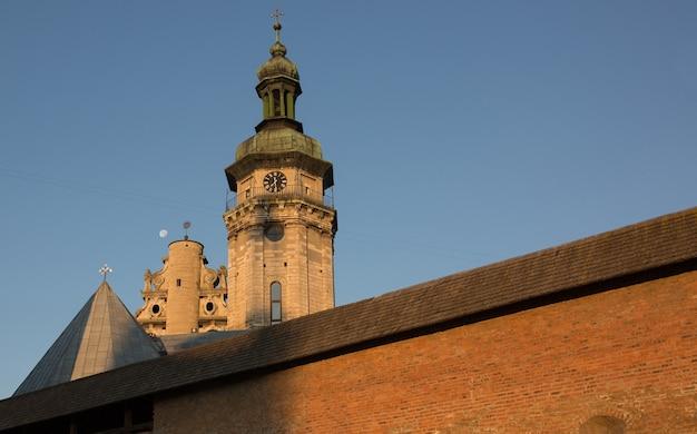 Vue d'une vieille église avec un monastère à lviv au lever du soleil