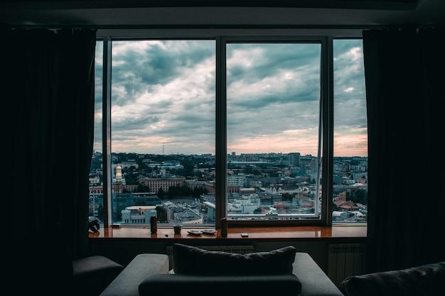 Vue de la ville depuis une grande fenêtre d'une maison haute