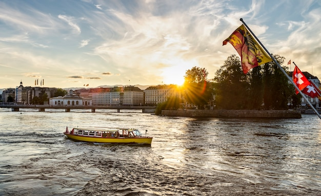 Vue sur la ville de genève au coucher du soleil, avec le drapeau suisse au premier plan.