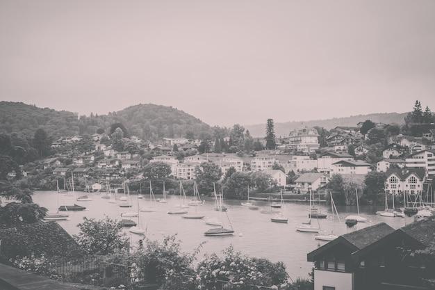 Vue sur la ville de spiez et le lac de thoune, suisse, europe. jour de soleil d'été, ciel nuageux bleu dramatique et montagnes lointaines
