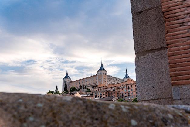 Vue de la ville de tolède depuis le pont de l'alcantara. vue de la ville entre les murs.