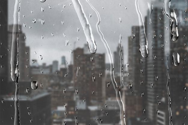 Vue sur la ville à travers la fenêtre avec des gouttes de pluie