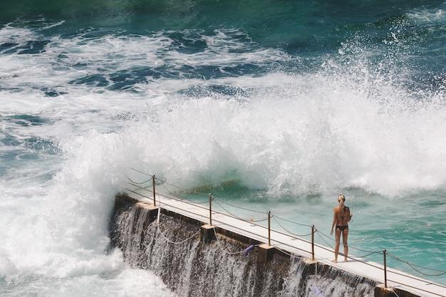 Vue à vol d'oiseau d'une femme blonde de race blanche en bikini noir à bondi beach, sydney, australie