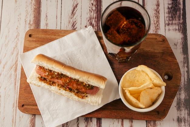 Vue à vol d'oiseau d'un hot-dog avec sauce chimichurri avec soda et chips de pommes de terre sur une table rustique. vue horizontale. concept de restauration rapide et de malbouffe.