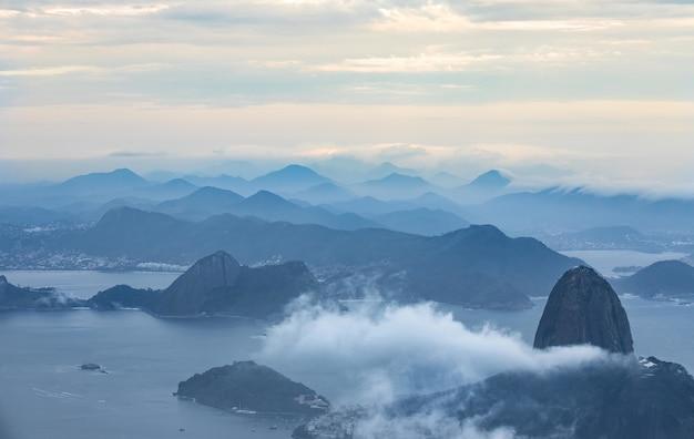Vue à vol d'oiseau d'un océan avec des montagnes entourées de nuages