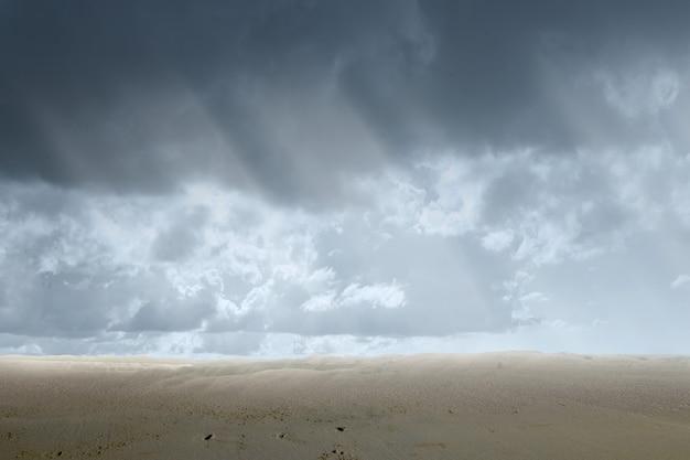 Vues sur les dunes de sable avec un ciel dramatique