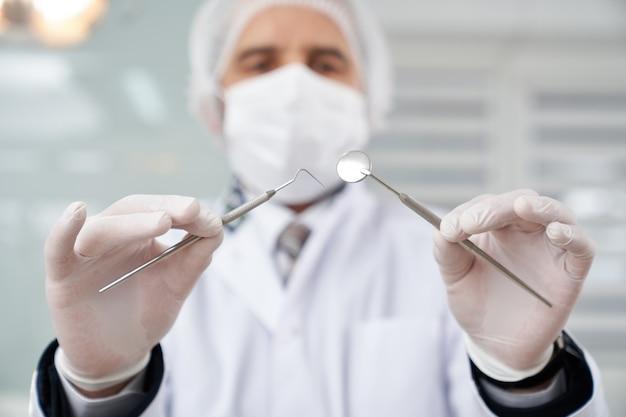 Vus de dessous d'un dentiste dans un masque tenant des instruments