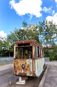 Wagon du vieux tram détruit rouillé en plein air à la journée ensoleillée.