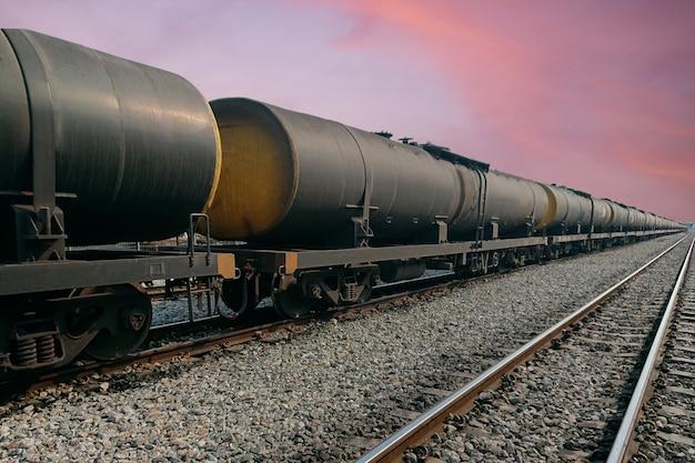 Wagons de train de fret noir ayant des pétroliers en attente sur les rails contre le ciel au lever du soleil