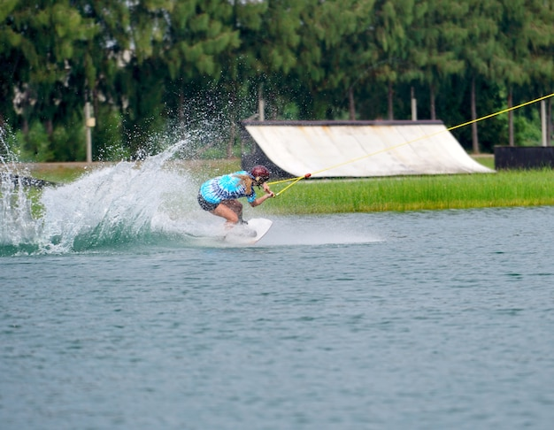 Wake boarding jump saut avec des éclaboussures d'eau dans le parc du wake.