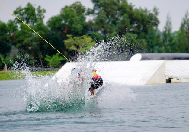 Wake boarding rider saut avec des éclaboussures d'eau dans le parc de wake