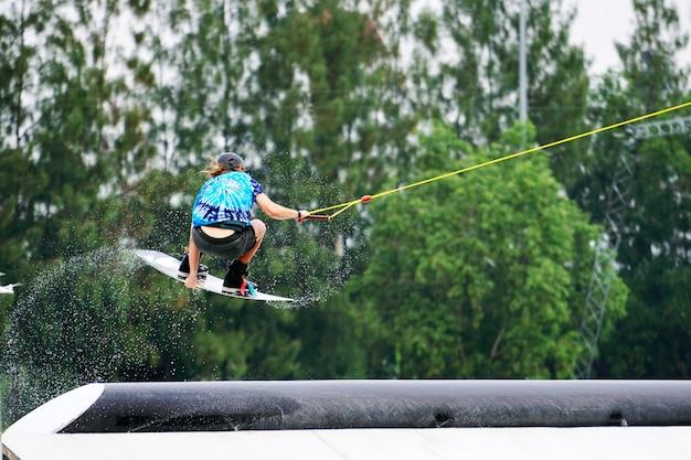 Wake boarding rider saut et vol avec des éclaboussures d'eau dans le wake park