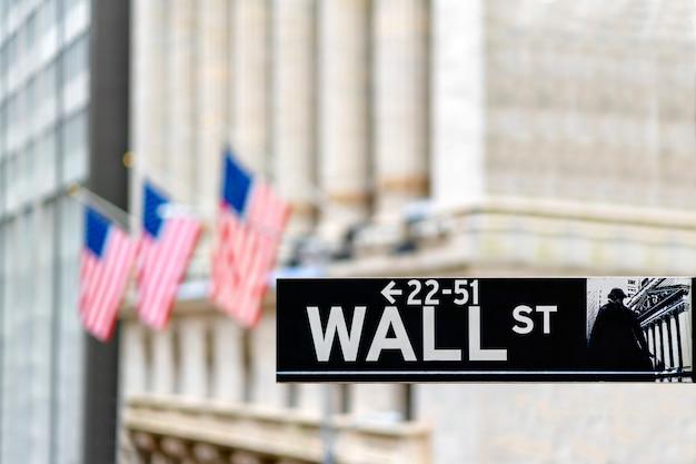 Wall street sign à new york city économie financière et quartier des affaires avec fond de drapeau national de l'amérique. commerce boursier et zone d'échange.