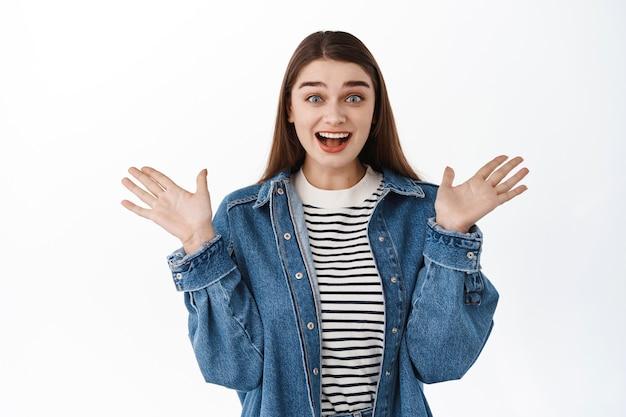Waouh super génial. une fille heureuse surprise regarde avec admiration, gagne quelque chose, tape des mains et se réjouit, haletant étonné et heureux, debout sur un mur blanc