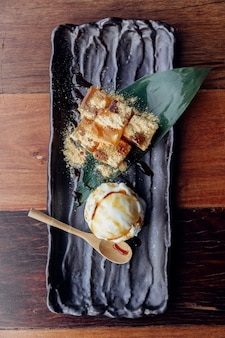 Warabi mochi servi avec une boule de glace à la vanille garnie de caramel.