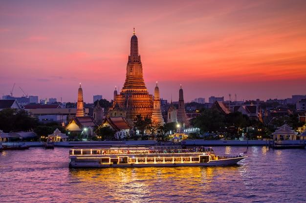 Wat arun et bateau de croisière au coucher du soleil, ville de bangkok, thaïlande