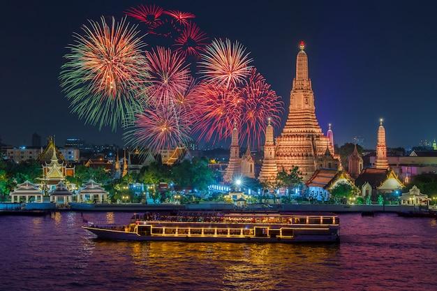 Wat arun et bateau de croisière dans la nuit sous la célébration du nouvel an, ville de bangkok, thaïlande