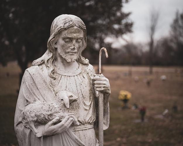 Weathered statue de jésus christ avec un mouton dans ses mains sur un arrière-plan flou