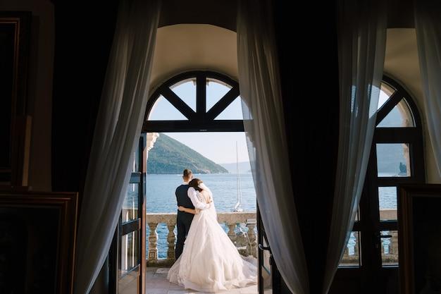 Wedding couple stand sur un balcon de l'hôtel avec vue sur la mer à travers une fenêtre antique ouverte fineart