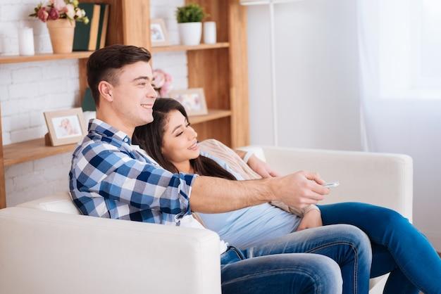 Week-end en famille. couple jovial gay assis sur un canapé pendant que l'homme change de chaîne de télévision