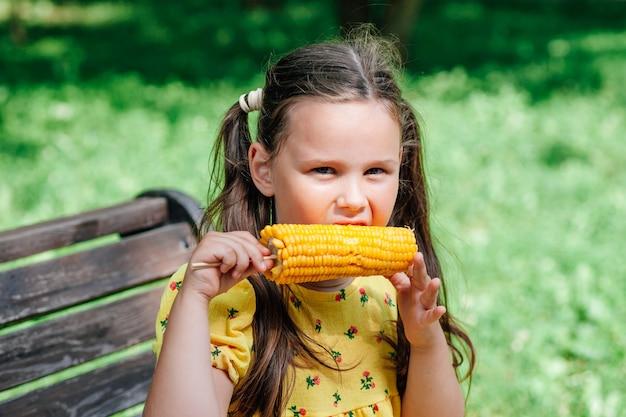 Week-end en famille dans le parc par une journée ensoleillée, l'enfant mange un délicieux maïs sucré