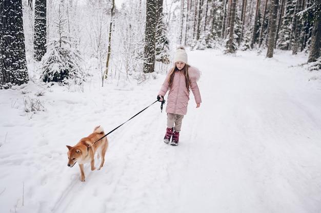 Week-end en famille heureuse - petite fille mignonne en vêtements chauds roses marchant s'amusant avec un chien shiba inu rouge dans la forêt d'hiver froid blanc neigeux à l'extérieur