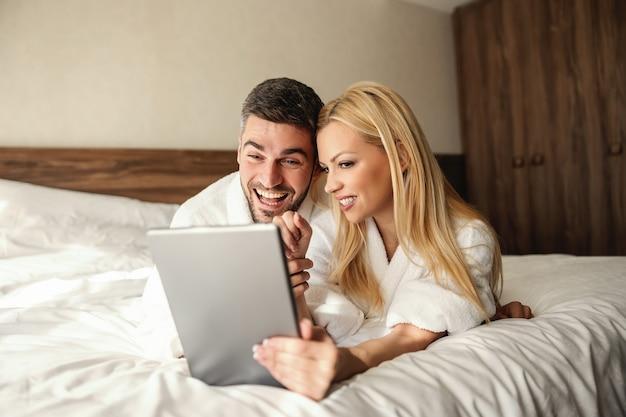 Week-ends de détente, réservations de spa en ligne depuis une chambre d'hôtel. le beau mec a son amant sur ses genoux et le serre doucement dans ses bras paiement en ligne dîner en ligne et réservation au spa carte de crédit