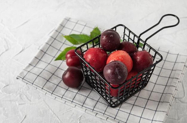 Weet fraîches délicieuses prunes rouges sur panier noir table en bois blanc fruits d'été