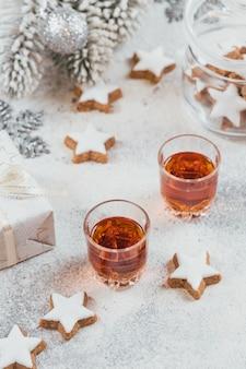 Whisky, brandy ou liqueur, biscuits et décorations de noël sur fond blanc