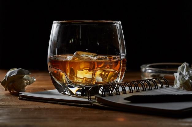 Whisky avec carnet de notes sur une table en bois