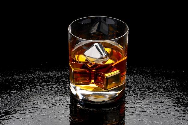 Whisky avec des cubes de refroidissement en acier sur verre sur une surface sombre