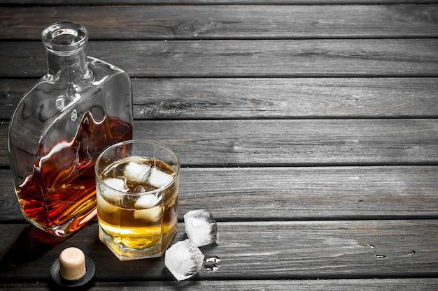 Whisky dans une bouteille en verre et un verre. sur bois