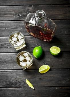 Whisky dans une bouteille et verres de glace et tranches de citron vert. sur bois noir